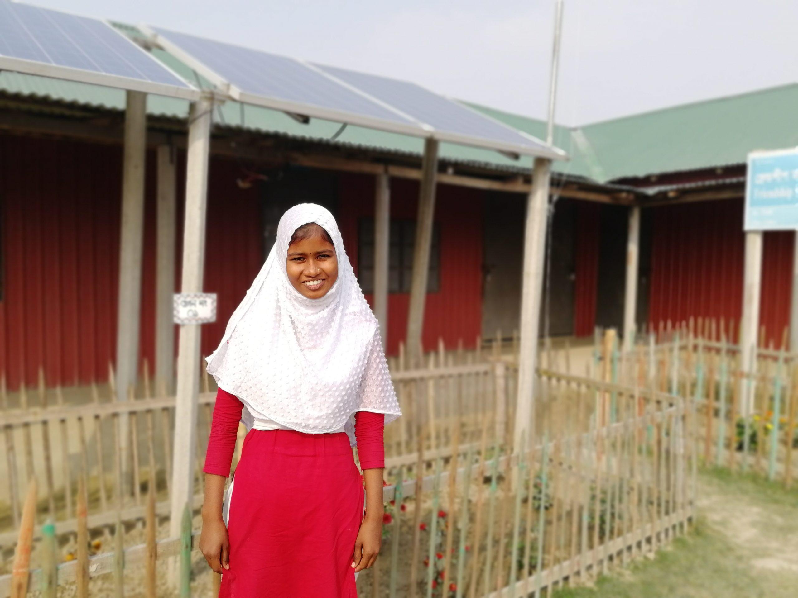 Alphona framför solcellerna på hennes skola